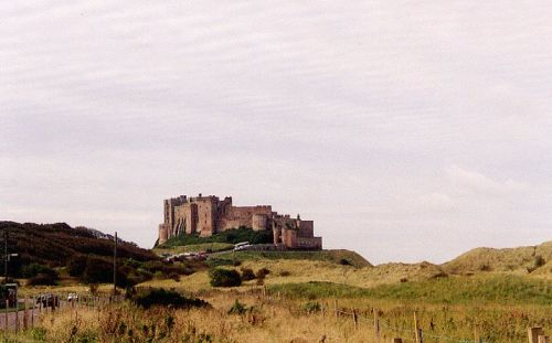 View of Bamburgh Castle from approaching coastal road.