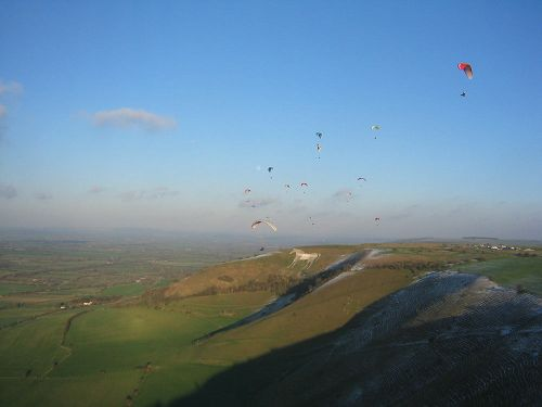 Paragliders flying over Westbury White Horse, Wiltshire