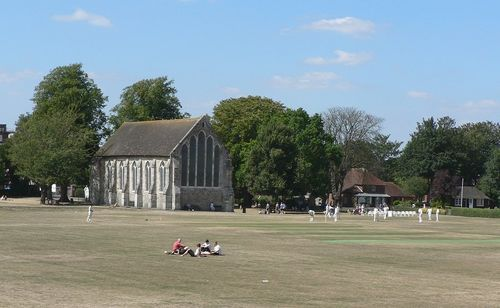 Guildhall museum in Priory Park, Chichester, with cricketers practicing before their match