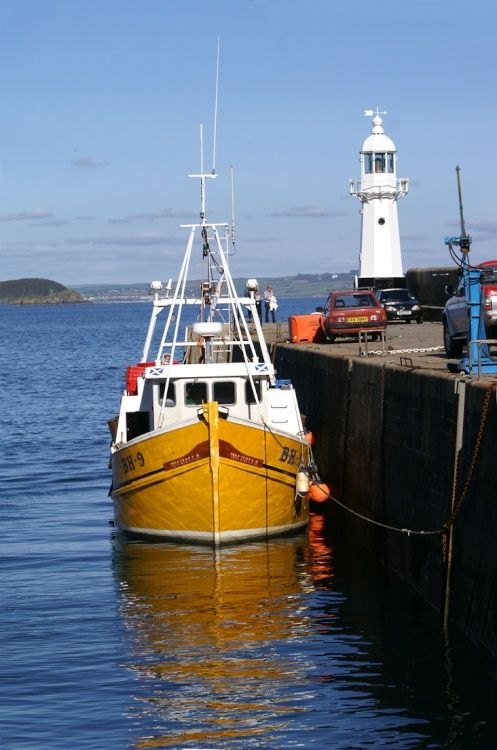 Fishing boat tied up at the harbour wall.
