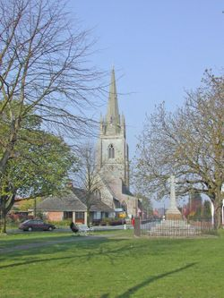 Helpringham in Lincolnshire showing the village green, war memorial and church.