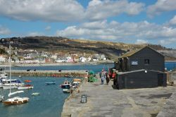 A view of the Marine Aquarium on the old Cobb with Lyme regis, Dorset, in the background.