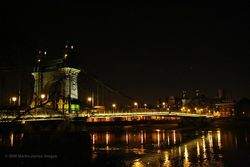 London Hammersmith Bridge at night from the towpath on the Barnes side of the River Thames.