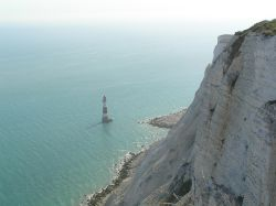The lighthouse at Beachy Head, East Sussex, dwarfed by the while cliffs above it.