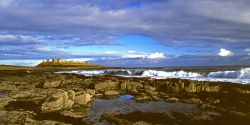 Dunstanburgh Castle, and shoreline seascape.