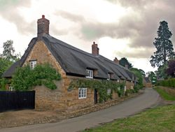 Thatched cottages under a gloomy sky
