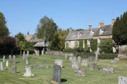 An attractive corner of the churchyard at Kingham Wallpaper