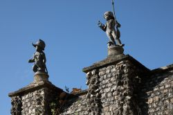 Statues of boy soldiers on flint wall near Greys Court House